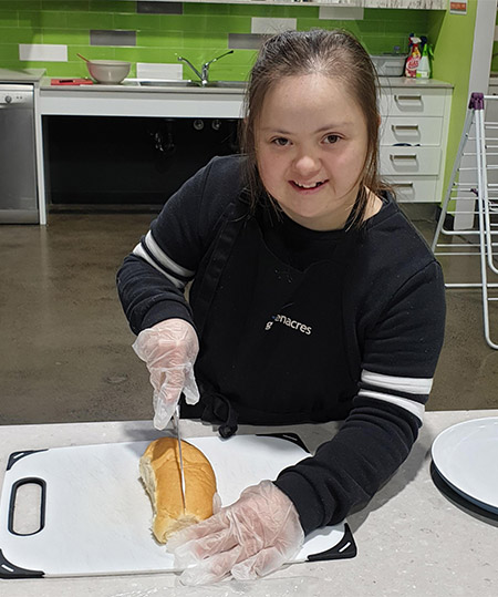 A young person smiling while cutting bread rolls